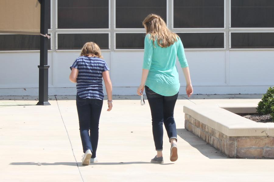 Junior Makenzie Johnson (r) takes a walk with her little sister as part of the Big Brother Big Sister Program.