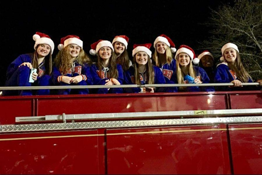 The varsity cheerleaders ride on a firetruck during the parade.