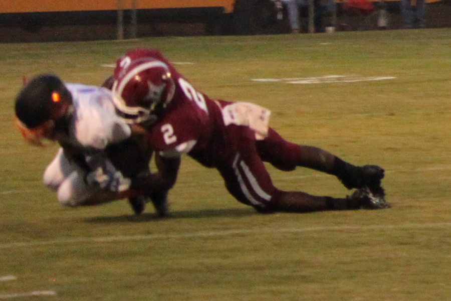 Junior Thaddeus Evans embraces the ball after being tackled by a defensive Wildcat.