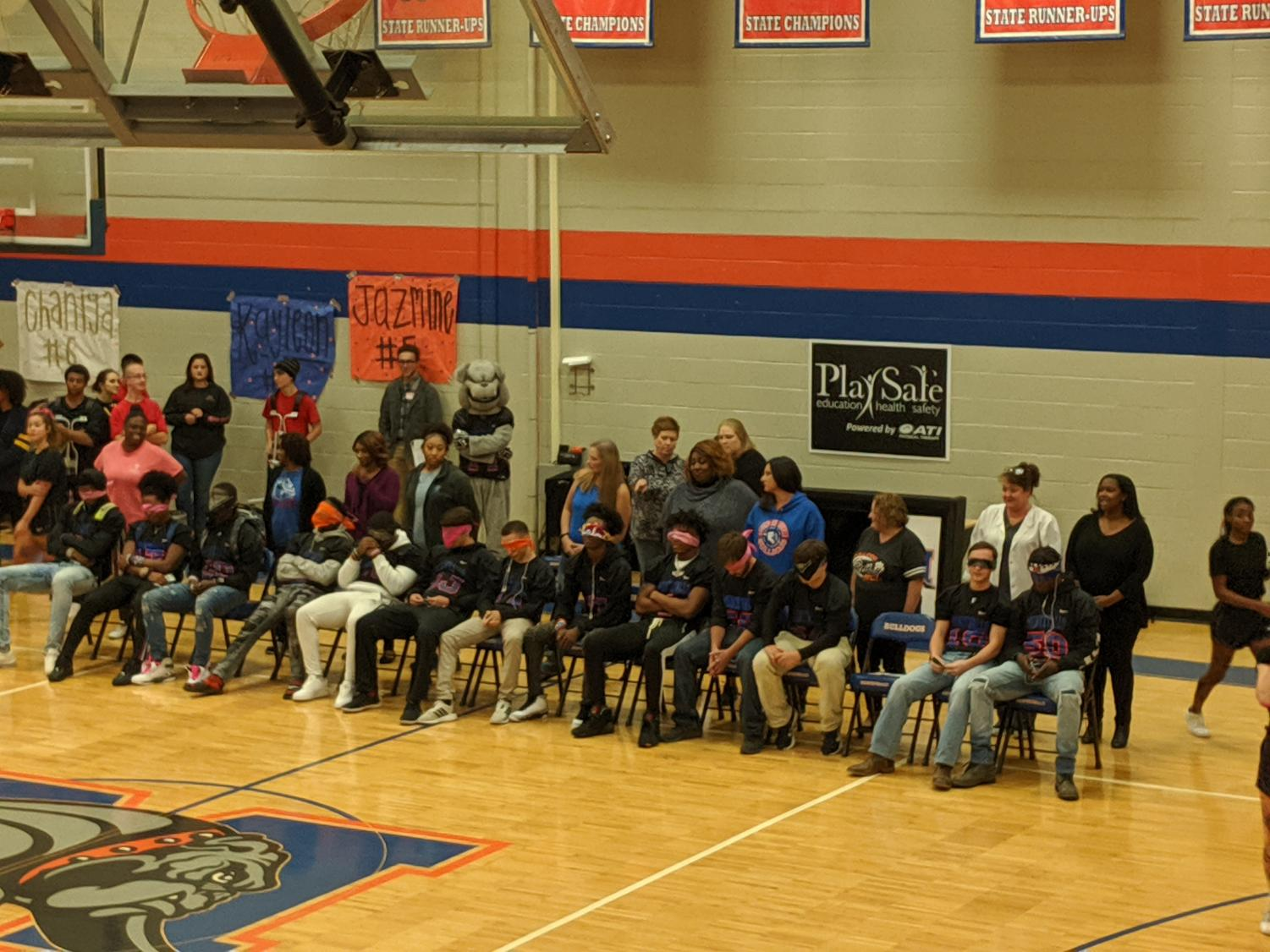 Senior football players were surprised by their moms at the pep rally.